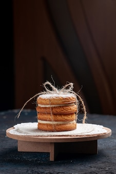Vista distante de frente, biscoitos sanduíche deliciosos amarrados no bolo azul escuro