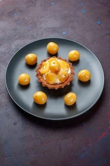 Vista distante de frente, um pequeno bolo cremoso com cerejas frescas dentro do prato na superfície escura