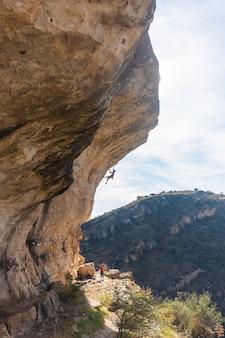 Vista distante de um escalador pendurado e escalador de uma formação rochosa.