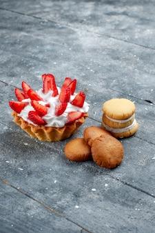 Vista distante frontal pequeno bolo cremoso com morangos fatiados e biscoitos em cinza