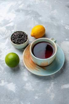 Vista distante frontal xícara de chá com limão fresco e chá seco na mesa de luz, cor cítrica de frutas do chá