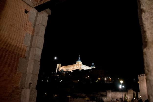 Vista do alcázar de toledo iluminada à noite. vista entre paredes.