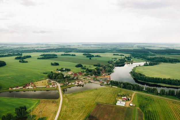 Vista do alto do lago em um campo verde em forma de ferradura e uma vila na região de mogilev.