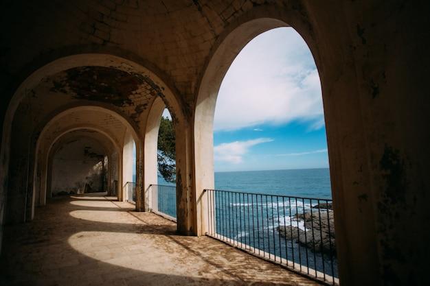 Vista do antigo edifício no oceano ou mar com colunas romanas e ruínas históricas na linha da costa mediterrânea.