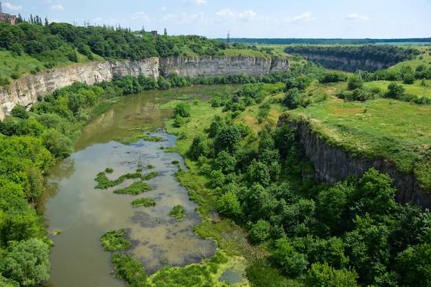 Vista do antigo rio que se tornou um pântano. as laterais estão cobertas de árvores. penhascos rochosos nas laterais