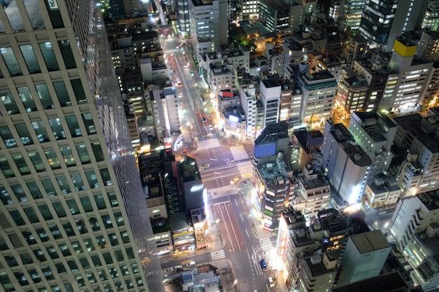 Vista do arranha-céu iluminar e tráfego na estrada no centro da cidade
