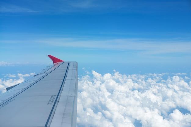 Vista do avião das janelas, voando alto acima das nuvens macias bonitas.