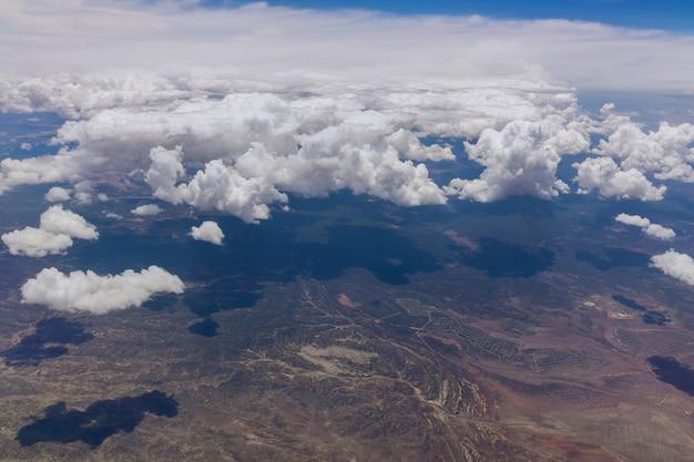 Vista do avião durante o vôo sobre nuvens fofas no deserto do novo méxico, eua