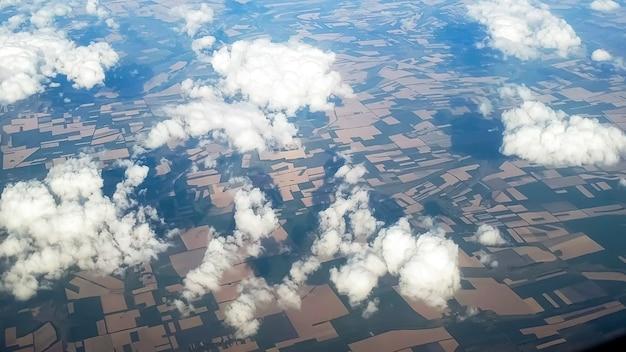 Vista do avião em nuvens voando sobre campos.