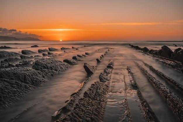 Vista do belo pôr do sol laranja no flysch da praia de sakoneta