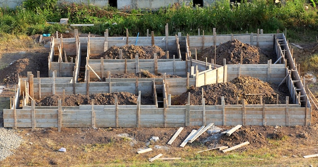 Vista do canteiro de obras e a fundação da casa de madeira no processo de preparação. adega de construção. fundação de concreto para um novo edifício