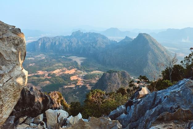 Vista do carste de pha ngern coberto de vegetação sob a luz do sol durante o dia em vang vieng, no laos