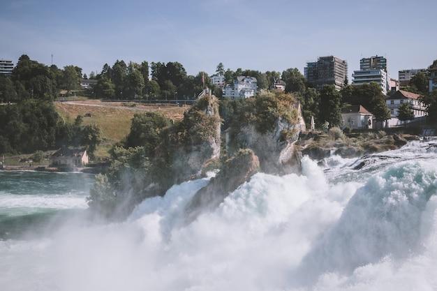 Vista do castelo laufen nas cataratas do reno é a maior cachoeira de schaffhausen, na suíça. paisagem de verão, clima ensolarado, céu azul e dia ensolarado