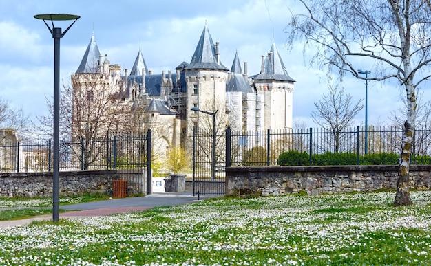 Vista do castelo saumur frança com gramado florescendo na frente.