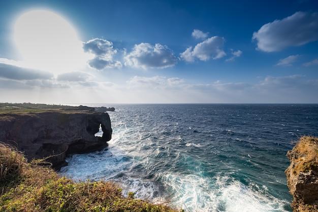 Vista do cenário, o céu azul, nuvem, sol redondo grande, o penhasco e o mar azul
