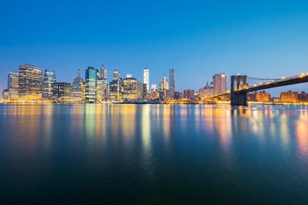 Vista do centro de manhattan em nova york ao anoitecer com arranha-céus iluminados sobre o east river