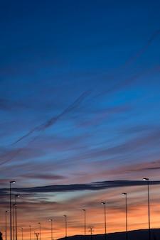 Vista do céu ao pôr do sol com postes de luz