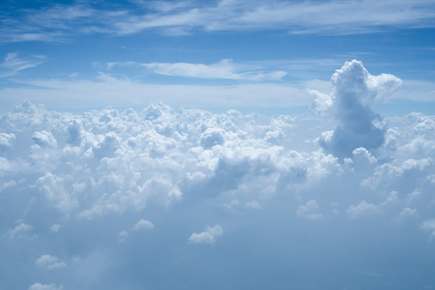 Vista do céu azul acima do branco principalmente nublado da janela do avião