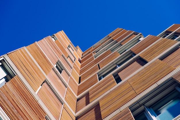 Vista do chão da fachada de um edifício moderno folheada em madeira ecológica sobre o céu azul limpo