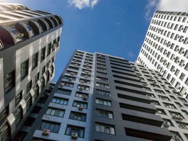 Vista do chão sobre os telhados de um edifício moderno de vários andares contra o céu azul e o sol forte