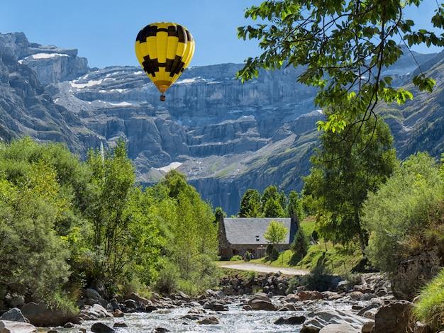 Vista do cirque de gavarnie com balão de ar quente amarelo, altos pirineus, frança