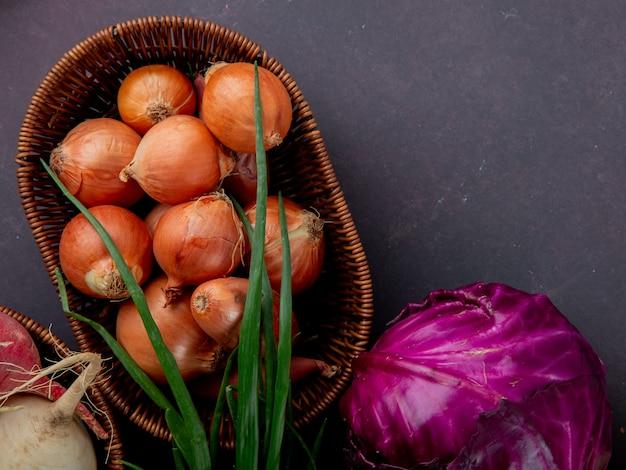 Vista do close-up da cesta cheia de cebola com couve roxa e cebolinha no fundo marrom com espaço de cópia