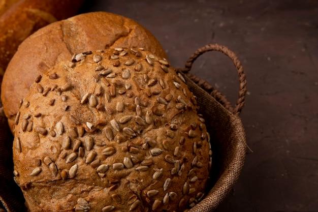 Vista do close-up da cesta de pães de espiga clássicos e semeados em fundo marrom com espaço de cópia
