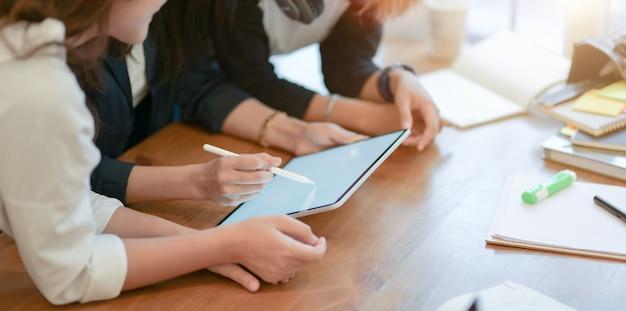 Vista do close-up da equipe de start-up jovem planejando o próximo projeto junto com o tablet
