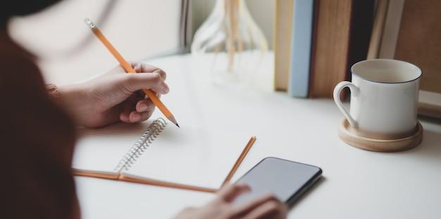 Vista do close-up da fêmea jovem, escrevendo sua idéia no notebook enquanto toca em seu smartphone