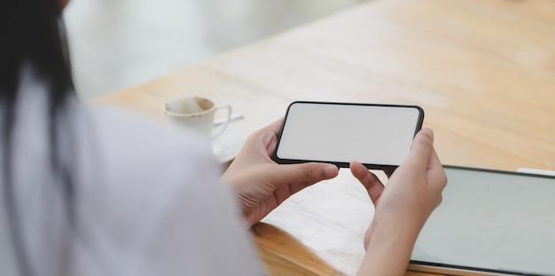 Vista do close-up da jovem médica, olhando para o smartphone de tela em branco