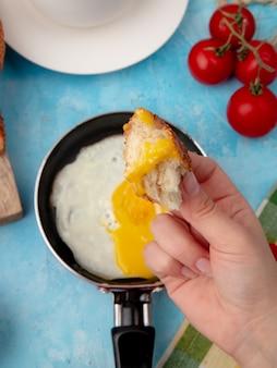 Vista do close-up da mão de uma mulher segurando o pedaço de pão sobre o ovo frito com tomate no azul