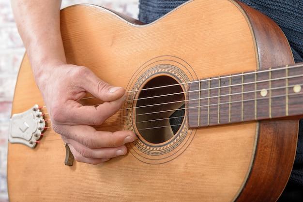 Vista do close-up da mão do homem tocando violão