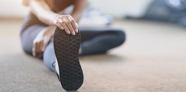 Vista do close-up da mulher com o corpo bronzeado e magro, esticando as pernas antes do exercício