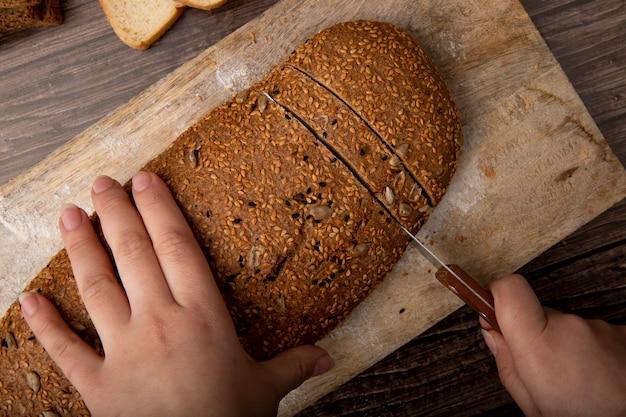 Vista do close-up da mulher mãos corte pão de sanduíche com faca na tábua sobre fundo de madeira