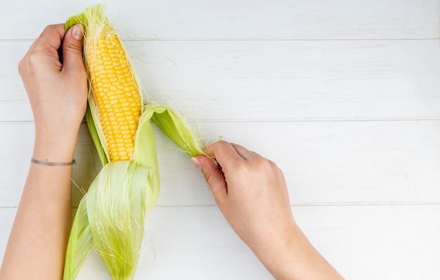Vista do close-up da mulher mãos limpeza espiga de milho na superfície de madeira com espaço de cópia