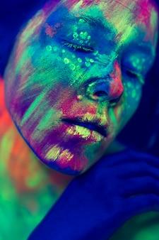 Vista do close-up da pessoa com maquiagem fluorescente