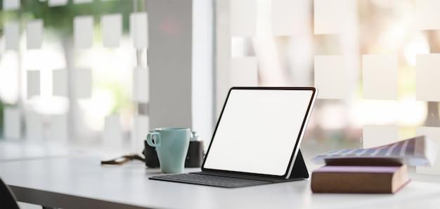 Vista do close-up da sala de escritório moderno com tablet digital de tela em branco com material de escritório