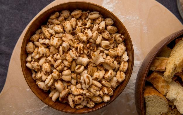 Vista do close-up da tigela de madeira com grãos na superfície de madeira e fundo marrom