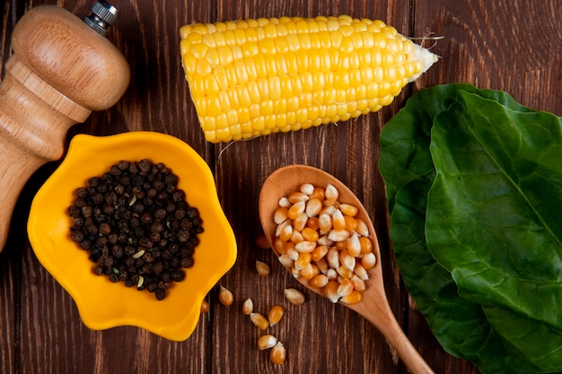 Vista do close-up da tigela de pimenta preta e sementes de milho em uma colher de pau com milho cortado e espinafre na mesa de madeira
