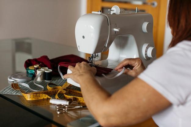 Vista do close-up das mãos de uma mulher sênior costurando máscaras