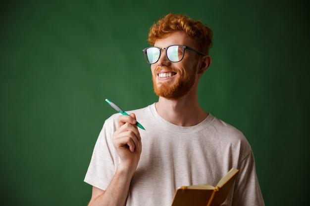 Vista do close-up de alegre jovem barbudo em camiseta branca, segurando um caderno e uma caneta