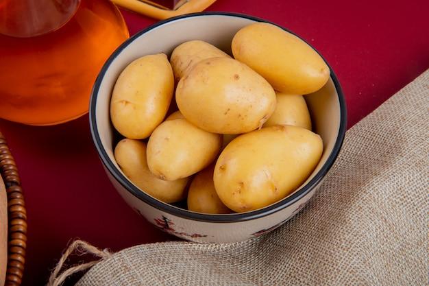 Vista do close-up de batatas novas em uma tigela com saco e manteiga derretida