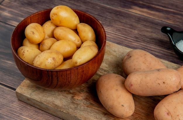 Vista do close-up de batatas novas na tigela e as brancas na tábua com sal na superfície de madeira