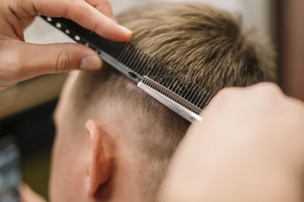Vista do close-up de cabeleireiro dando um corte de cabelo para um cliente