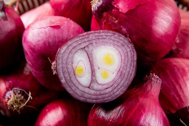 Vista do close-up de cebola roxa cortada e cebola vermelha inteira