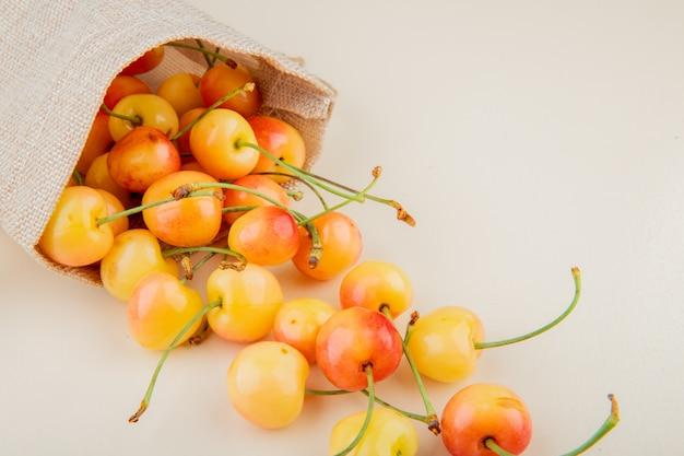 Vista do close-up de cerejas amarelas derramando fora do saco na superfície branca Foto gratuita