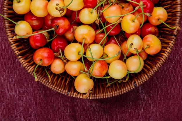 Vista do close-up de cerejas vermelhas e amarelas na cesta no pano de bordo