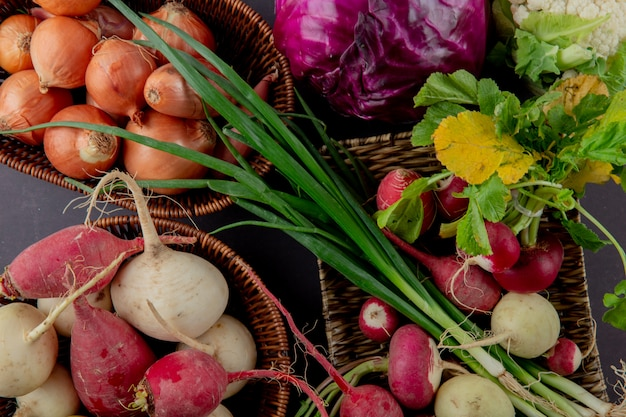 Vista do close-up de cestas e prato de legumes como cebolinha rabanete cebola e couve no fundo marrom