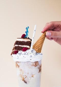 Vista do close-up de delicioso milk-shake com casquinha de sorvete e bolo