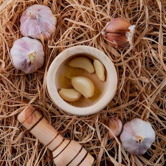 Vista do close-up de dentes de alho descascados no triturador de alho e bulbos de alho no fundo de palha
